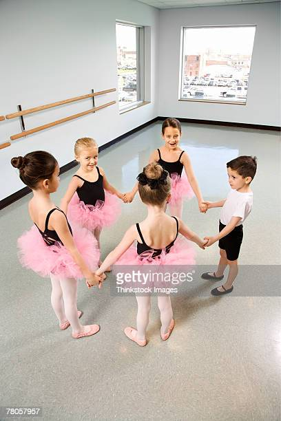 Ballet students standing in a circle and holding hands