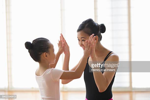 Ballet teacher congratulating young student.