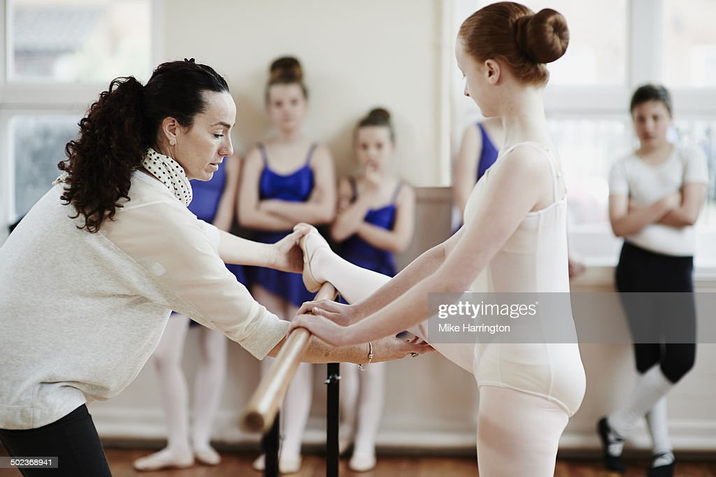 Ballet teacher helping dancer in dance studio : Stock Photo