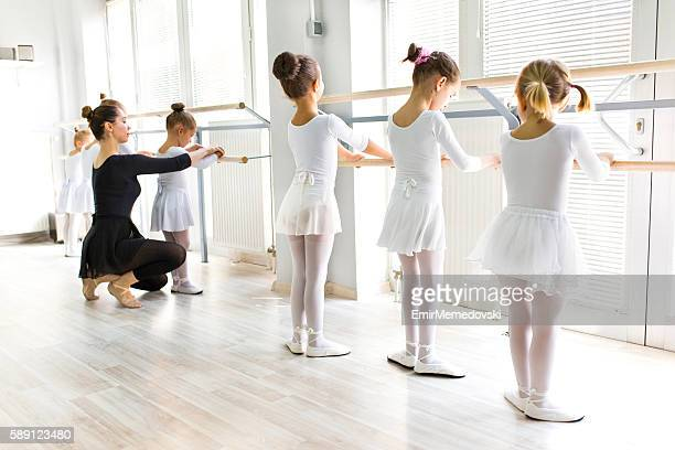 ballet teacher helping girls with postures during ballet class. - little girls undies stock pictures, royalty-free photos & images