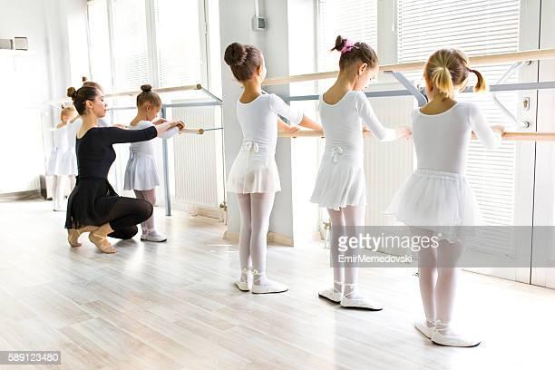 ballet teacher helping girls with postures during ballet class. - バレエ ストックフォトと画像