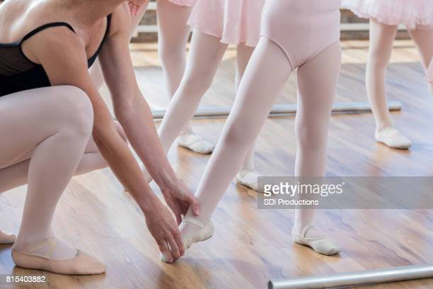 ballet teacher helps young student point toes - little girls dressed up wearing pantyhose stock photos and pictures