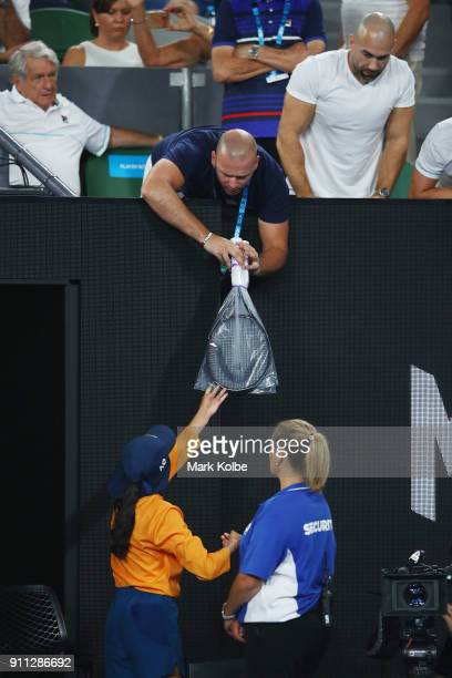 A ballkid delivers racquets belonging to Marin Cilic of Croatia to his player's box in his men's singles final match against Roger Federer of...