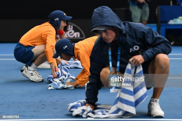 Ballkids dry the court after rain fell during the men's singles first round match between Italy's Andreas Seppi and France's Corentin Moutet on day...