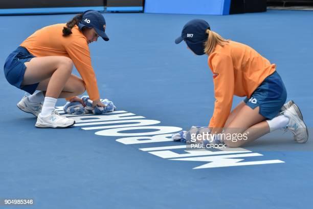 Ballkids wipe the court during the women's singles first round match between Slovakia's Dominika Cibulkova and Estonia's Kaia Kanepi on day one of...