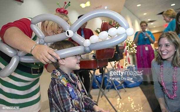 Balloon artist Johnna Perry places a shark on Donovan Campbell as his mother Kelli Campbell lookes on during festivities at the Snowball Express on...