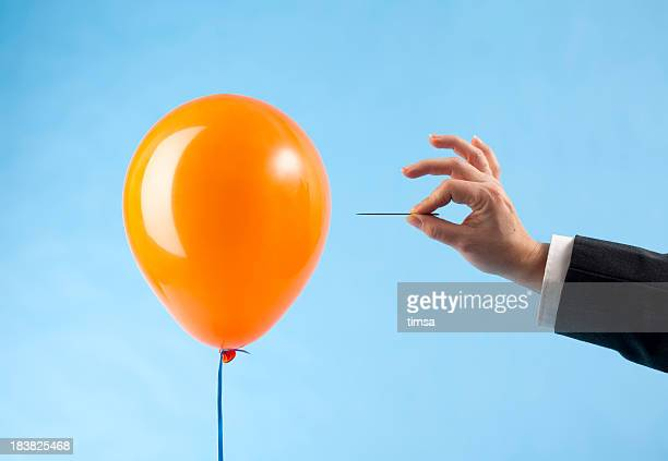 balloon attacked by hand with needle - exploding stock pictures, royalty-free photos & images