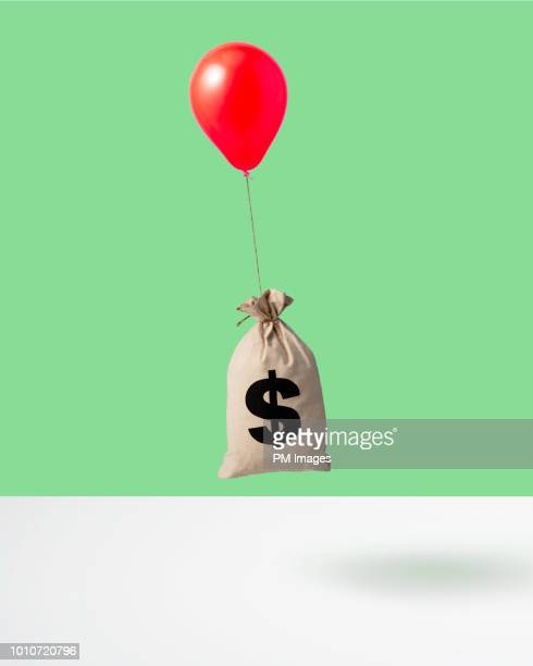 balloon carrying money bag, studio shot - finance and economy stock pictures, royalty-free photos & images