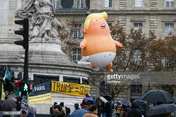 A balloon depicting the US President Donald Trump wearing a diaper flies over the heads of people protesting against the US leader at the Place de la...