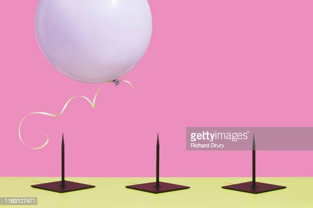 balloon flying over metal spikes - journey stock pictures, royalty-free photos & images