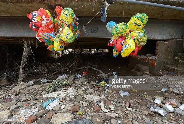 Balloon for sale hang next to the Ciliwung river following heavy floods in Jakarta on January 23 2013 A spokesman for Indonesian National Disaster...