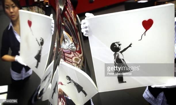'Balloon Girl' 2003 by artist Banksy is held by Bonham's Andrea Lee and is reflected in a mirror polished vase entiled 'B.O.O.P. By Ron Arad on...