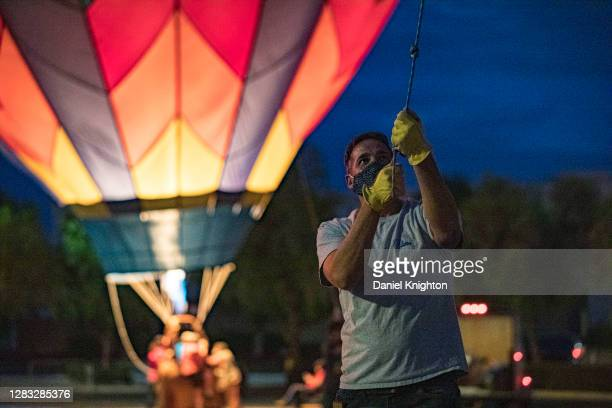 Balloon owner David Woodland of Cielo Balloons holds a tether at the Hot Air Halloween Balloon Glow on October 31, 2020 in Temecula, California. As...
