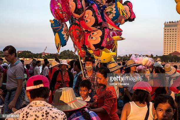 A balloon street seller stands in the middle of thousands of people attending the first day of the Water Festival on November 13 2016 in Phnom Penh...