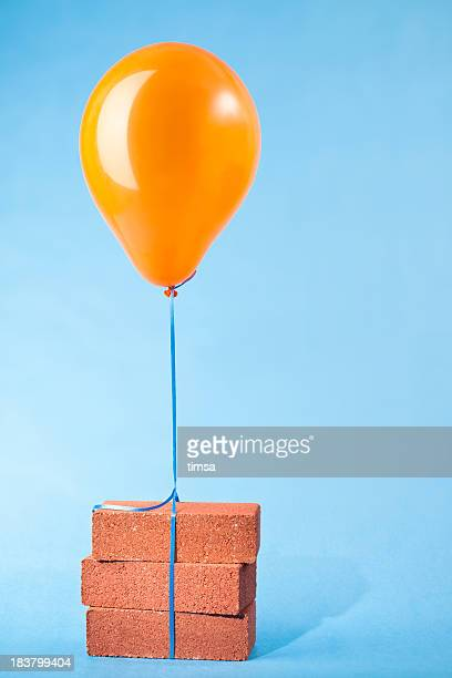 balloon tethered to three red bricks - over burdened stock pictures, royalty-free photos & images
