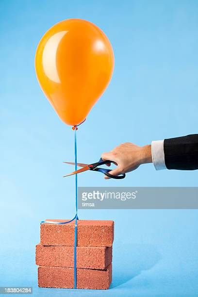 Balloon tethered to three red bricks, scissors cutting string