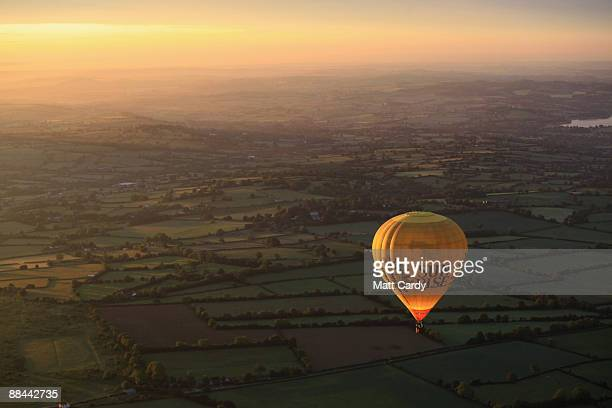 A balloon that has just taken off from the runway of Bristol International Airport flies towards the sun as it rises over countryside south of...