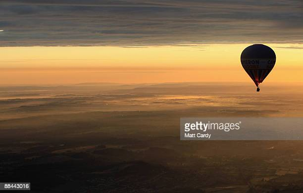 A balloon that has just taken off from the runway of Bristol International Airport flies towards the sun as it rises over Bristol on June 12 2009 in...