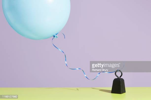 a balloon tied to a metal weight - restraining stock pictures, royalty-free photos & images