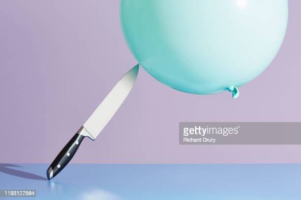 a balloon touching kitchen knife - fear stock pictures, royalty-free photos & images