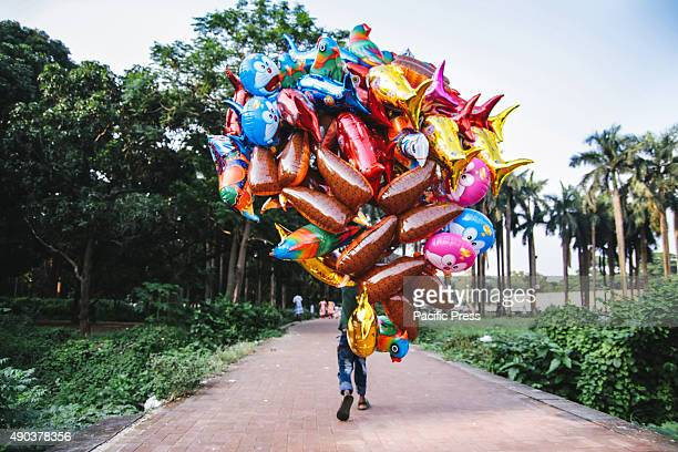 A balloon vendor carries bunch of ballons for sale in a park Some people in Dhaka earn living through balloon selling in the public