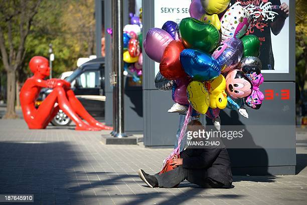 A balloon vendor sits on the ground outside a mall as he waits for customers in Beijing on November 11 2013 Chinese state media on November 10 raised...