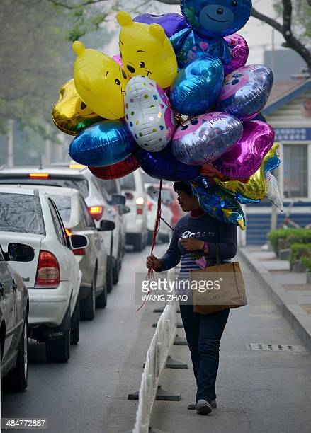 A balloon vendor waits for customers as she walks along a road in the central business district in Beijing on April 14 2014 Chinese exports and...