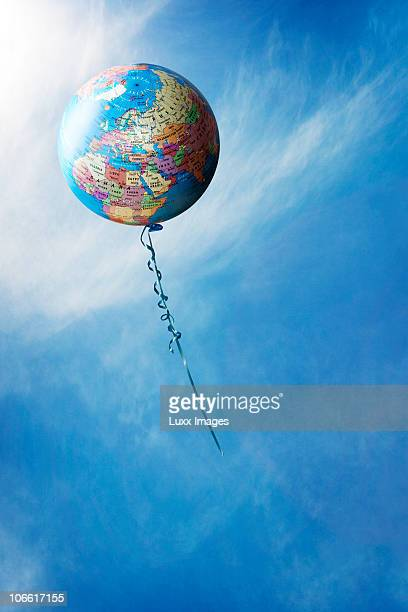 Balloon with world map against blue sky