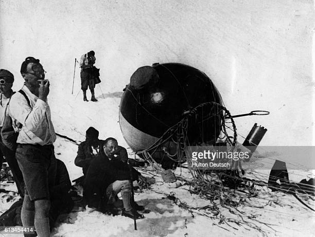 Balloonists and scientists Paul Kipfer and Jean Piccard rest near their pressurized balloon gondola after their successful ascent into the upper...