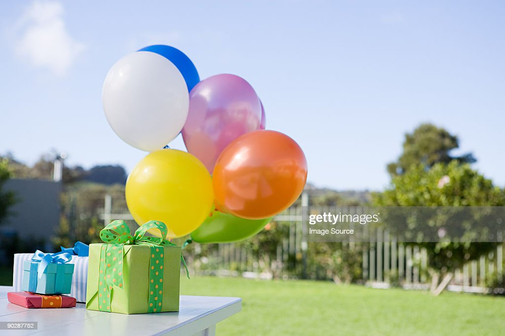 Balloons and birthday presents on table in garden : Stock Photo