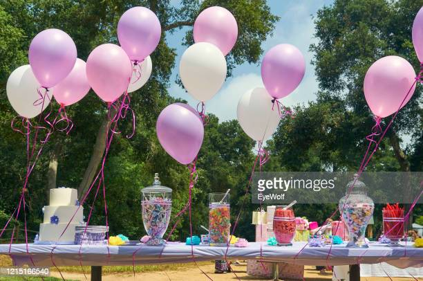 balloons and candy laid out on a table outside for a baby shower - baby shower stock pictures, royalty-free photos & images