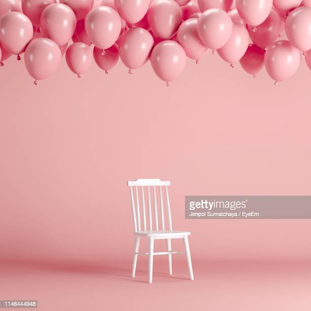 balloons and chair against pink background - chair stock pictures, royalty-free photos & images