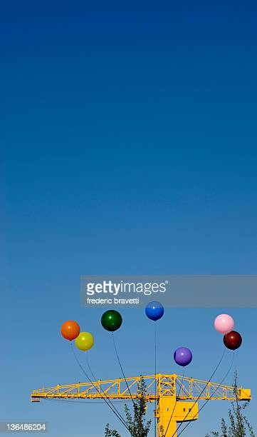 Balloons and crane against blue sky
