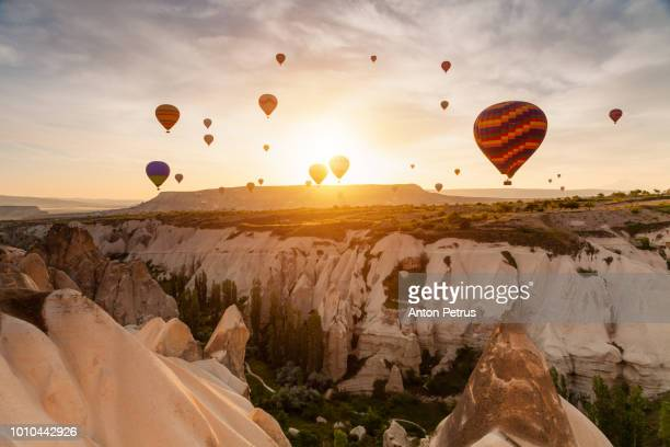 Balloons at sunrise over the beautiful landscape in Cappadocia, Turkey