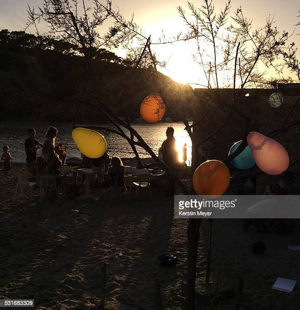 balloons during sunset this scenery is a children's birthday party on a beach in ibiza during sunset