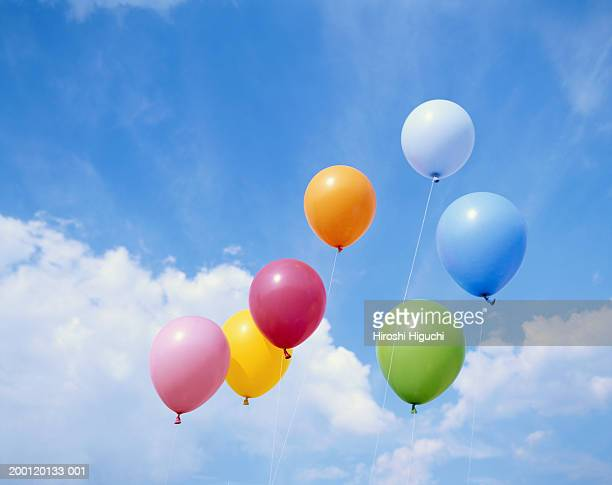 Balloons floating against cloudy sky, low angle view