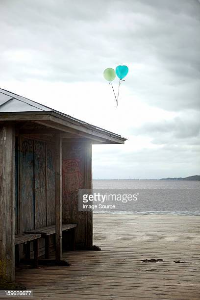 Balloons floating by old seaside shelter, Flensburg, Germany
