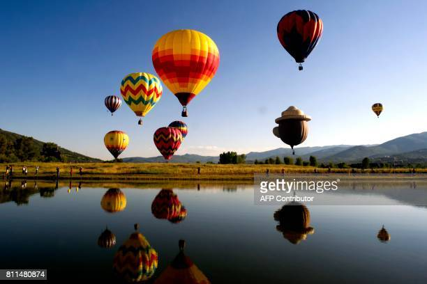 TOPSHOT Balloons fly in the sky as their reflections are cast down onto Bald Eagle Lake during the 36th Annual Hot Air Balloon Rodeo in Steamboat...