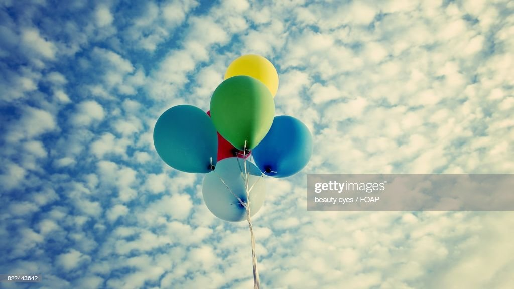 Balloons flying against cloud sky : Stock Photo