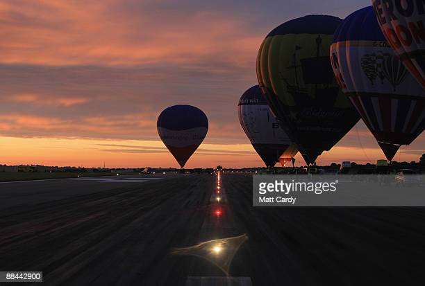 Balloons prepare to take off from the runway of Bristol International Airport fly as the sun rises over Bristol on June 12 2009 in Bristol England In...