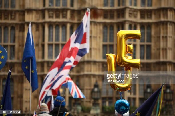 Balloons spelling EU fly beside Union Jack and European Union flags outside the Houses of Parliament in Westminster on December 10 2018 in London...