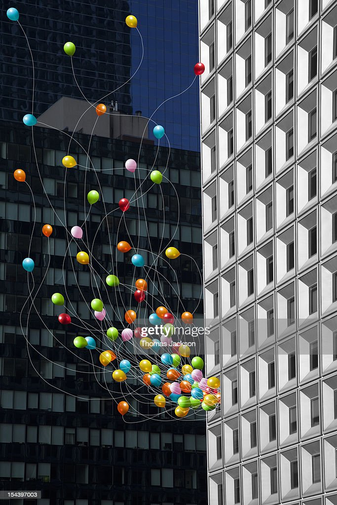 Balloons streaming from office building window : Stock Photo