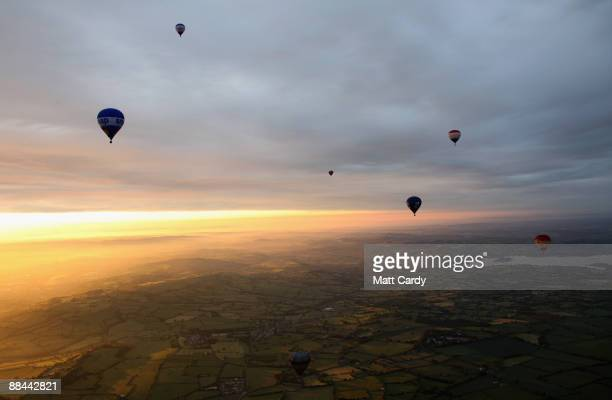 Balloons that have just taken off from the runway of Bristol International Airport fly towards the sun as it rises over Bristol on June 12 2009 in...