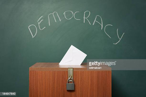 Ballot Box Before Green Blackboard With Word Democracy Written On