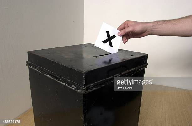 Ballot box Man casting ballot into ballot box whilst voting in election vote