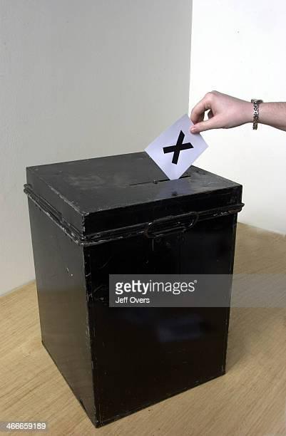 Ballot box Woman casting ballot into ballot box whilst voting in election vote