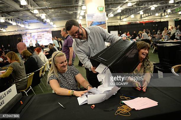 Ballot boxes are emptied at the counting centre at Doncaster Racecourse northern England on May 7 2015 after polls close during the British general...