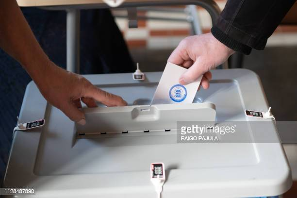 A ballot is casted in a voting box during Estonia's general election in a voting station in Tallin on March 3 2019 Estonias centreleft coalition is...