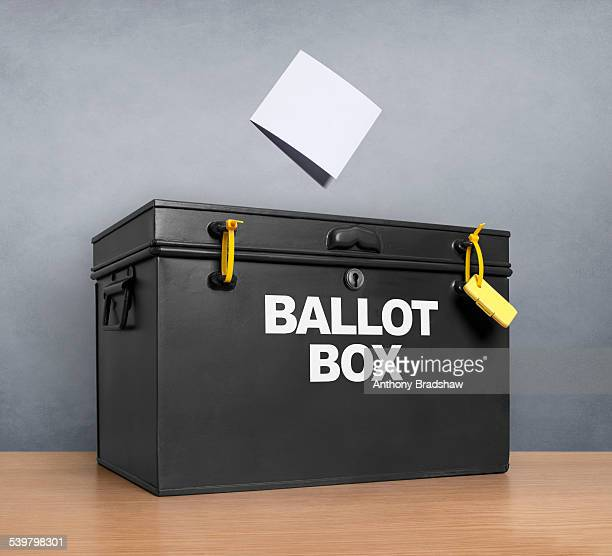 ballot paper poised above the ballot box - ballot box stock pictures, royalty-free photos & images