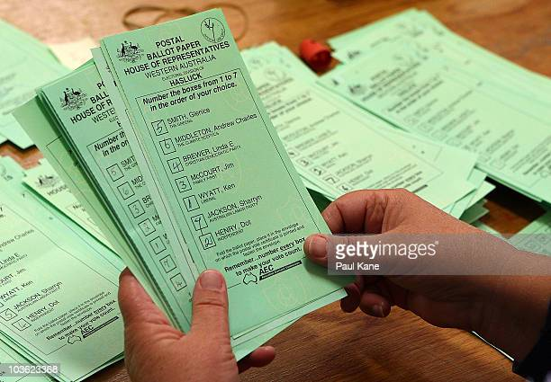 Ballot papers are scrutinised as the counting of absentee and postal votes for the marginal seat of Hasluck in Western Australia begins on August 25...